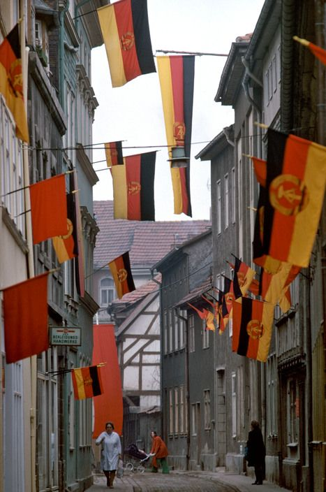 A street in the old city center of Mehlhausen in Thuringia, East Germany adorned with tricolor flags of the German Democratic Republic and red flags, 1974.
