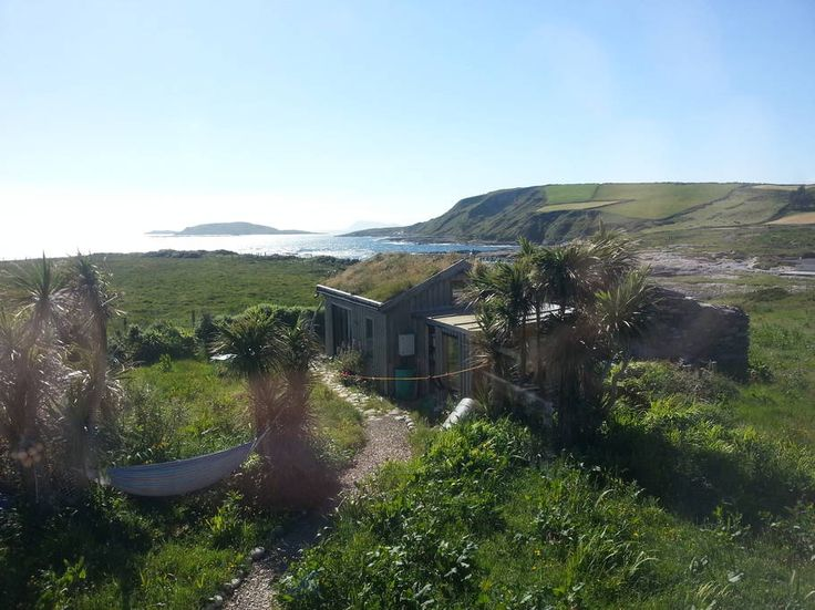 Cabin in Kilcatherine, Eyeries, Beara, Ireland. This snug, grass-roofed cabin offers panoramic views of the Atlantic Ocean. Enjoy a warm Irish welcome, mountain walks on the Beara Way or snorkling on nearby reefs. Sample local seafood or stoke up the wood-burning stove and savour the tranquilit...