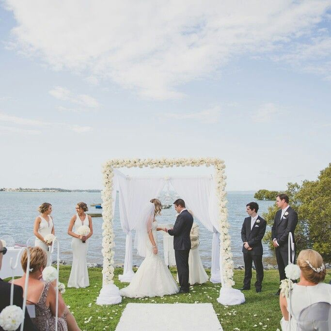 Absolutely divine floral wedding arbour covered with fresh roses for a white wedding.  Ceremony decor and floral arbour by Brisbane Wedding Decorators ♡ Www.brisbaneweddingdecorators.com.au