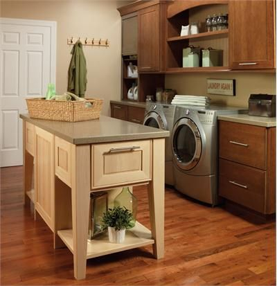 By Merrilat: Durability and spaciousness are key factors in this traditional laundry area. Rich wood cabinetry coordinates with hardwood floors for a timeless appeal. Features such as the side-by-side, front-loading washer/dryer set and a large work area for folding fresh loads are equally attractive when it comes to getting the job done.