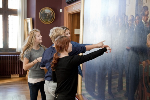 Girls from the eldest group of schoolchildren studying a history painting central to their topic; the birth of the Danish constitution.