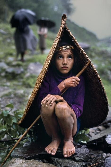 Steve McCurry  NEPAL. Pokhara. 1985. A boy shelters from the rain under a woven straw 'umbrella hat'.