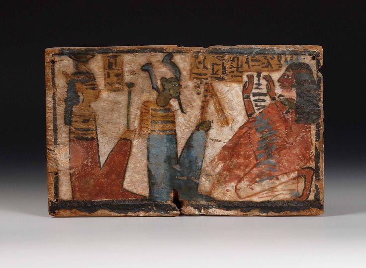 """Taula decorada. Fusta estucada i policromada. Dinastia XIX-XX. Darrere Osiris apareix Neftis, a la qual reconeixem gràcies a la seva corona identificativa que representa el seu nom amb els símbols jeroglífics. Literalment el seu nom significa """"senyora de la casa"""" identificat per una casa amb un cistell al capdamunt. (1320 – 1085 a.C) (Museu de Montserrat)"""