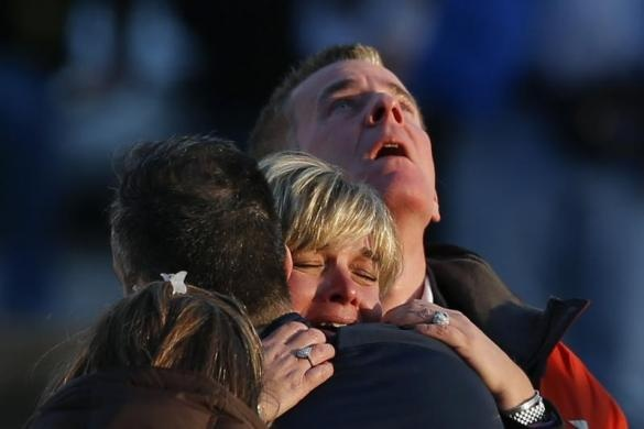 Lynn and Christopher McDonnell, the parents of seven-year-old Grace McDonnell, grieve near Sandy Hook Elementary after learning their daughter was one of 20 school children and six adults killed after a gunman opened fire inside the school in Newtown, Connecticut, December 14, 2012. REUTERS-Adrees Latif