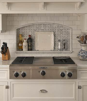 Backsplash Storage Niche ~ I love the shelf ~ A subway-tile backsplash surrounds an arched niche that provides convenient storage for spices and cooking oils. The arch reinforces the old-time theme. The slightly darker hues found beneath the arch add a subtle difference and mesh well with the stainless-steel cooktop.