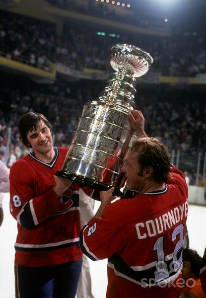 Yvan Cournoyer (12) and Serge Savard (18) raise the Stanley Cup for the Montreal Canadiens
