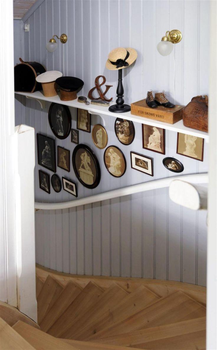 Hattar på rad ovanför gamla fotografier i svarta ramar som arrangerats prydligt.