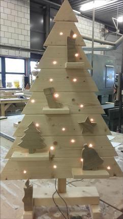 leuke houten kerstboom met versiering en lampjes.