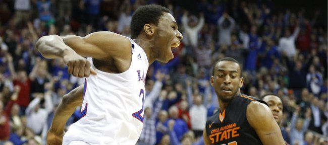 Kansas guard Andrew Wiggins celebrates after a lob dunk before Oklahoma State guard Markel Brown during the second half on Thursday, March 1...