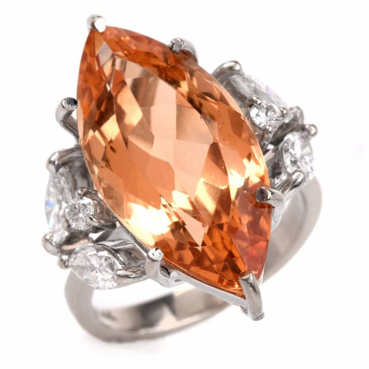 Imperial Topaz Diamond Gold Cocktail Ring, This Vintage cocktail ring with a naturaI and untreated marquise-faceted Imperial topaz of an enchanting intense golden yellow color approx. 10.35, marquise and round-faceted diamonds is crafted in solid 18K yellow gold and weighs 7.2 grams. The translucent marquise-faceted imperial topaz is secured by 6 prongs atop an openwork gallery and is flanked by bejeweled shoulders...c 1940