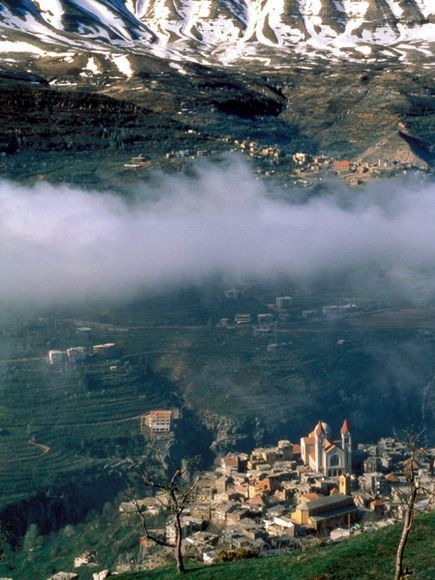 Snowcapped mountains rise above Bcharre, a town in the Maronite Christian heartland along the Qadicha Valley in northern Lebanon.