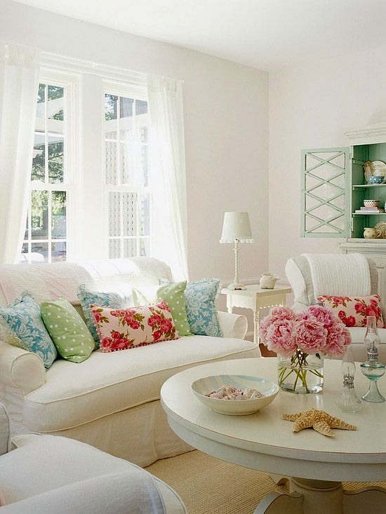 White Out - All-white rooms need a dose of personality. Throw pillows bring in a pop of green, blue, and pink in cottage-inspired patterns. But the addition is small enough as not to disturb the ambience of the crisp, white room. Different textures, like the bowl of shells, starfish, and a sisal rug, add depth to the room