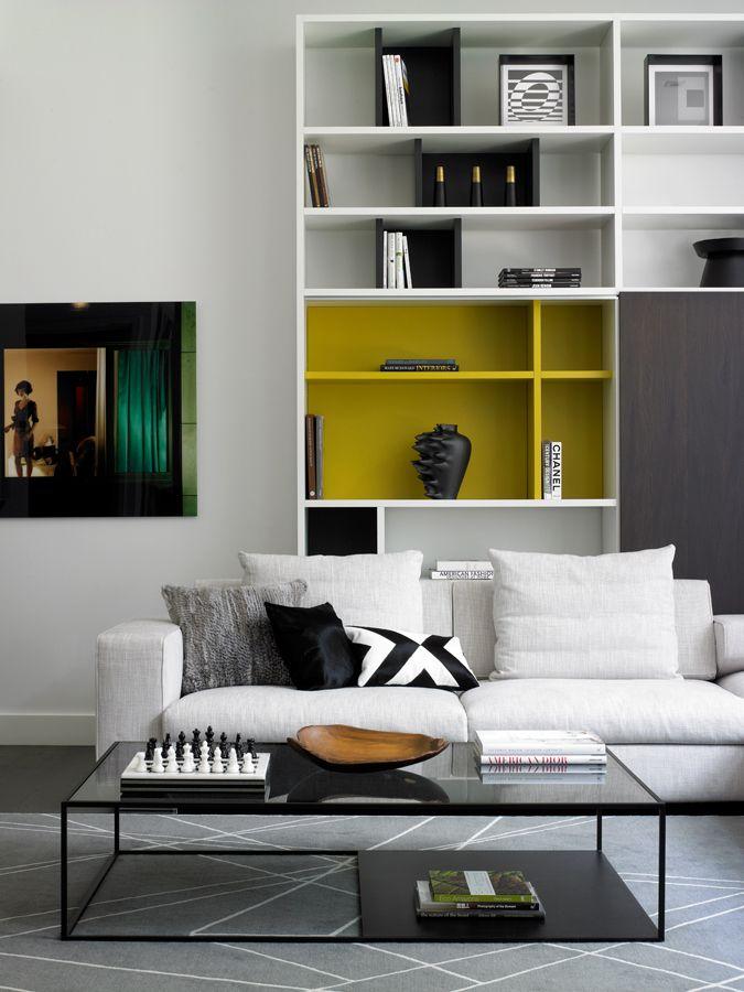 SALA ESTAR. Prateleiras além de organizar os objetos, quando colorida de amarelo faz parte da decoração.