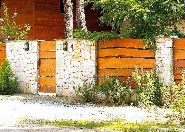 Przykład z poziomo ułożonymi deskami ogrodzenia, wplecionymi pomiędzy kamienne słupy.  - zdjęcie