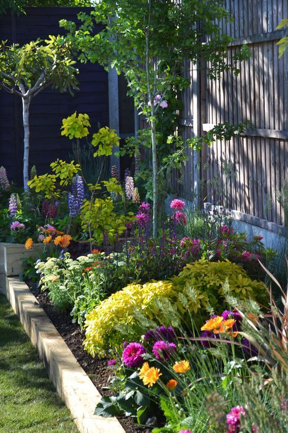 Colourful raised border in pinks, orange and yellow #gardenideas #raisedbeds