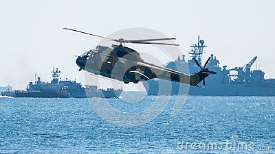 War simulation, helicopter over water at low altitude. Battle ships in background. Navy day parade, August 2012, Constanta, Romania.