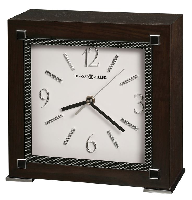 Reese Mantel Clock. This contemporary mantel clock has beautiful silver accents and would be perfect for any room. Black Coffee finished mantel clock on select hardwoods and oak veneers with polished chrome-finished, plated metal feet. Features flat glass over the dial, accented by a black border with white dot pattern and polished black and chrome-finished square embellishments on the corners. Quartz, battery-operated movement requires one AA sized battery.