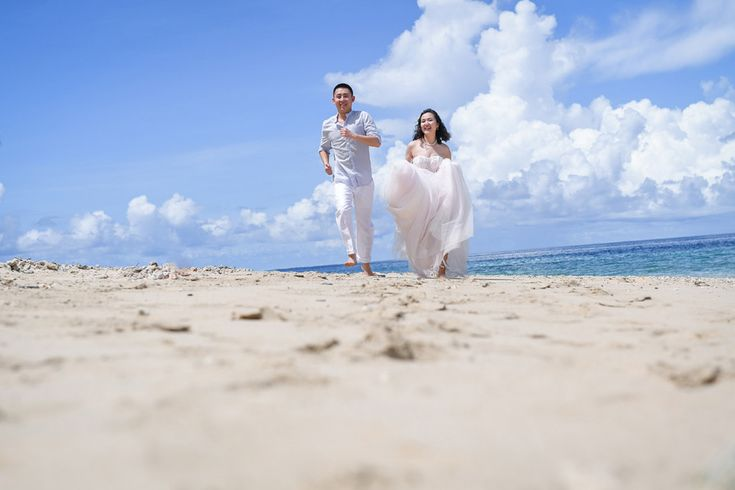 Couple running by the beach for their wedding photography  at Paradise Cove island resort in Fiji by Anais Photography