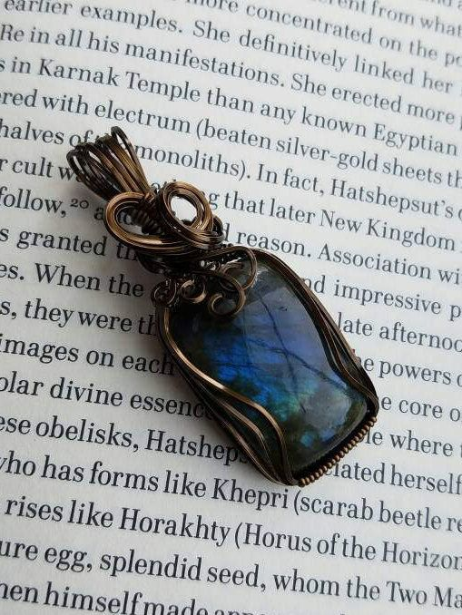This beautiful labradorite pendant is elegantly wrapped with antiqued brass colored wire to accent the gorgeous flashes of blue and green. This pendant will look gorgeous with any outfit whether it is casual or formal. It is said that labradorite fell from the aurora borealis and brought with it magical properties of healing and balance. Materials: rainbow blue labradorite cabochon with antiqued brass color enameled wire  Approximate measurements: 2.25 inches long by 7/8 inches wide by 3...