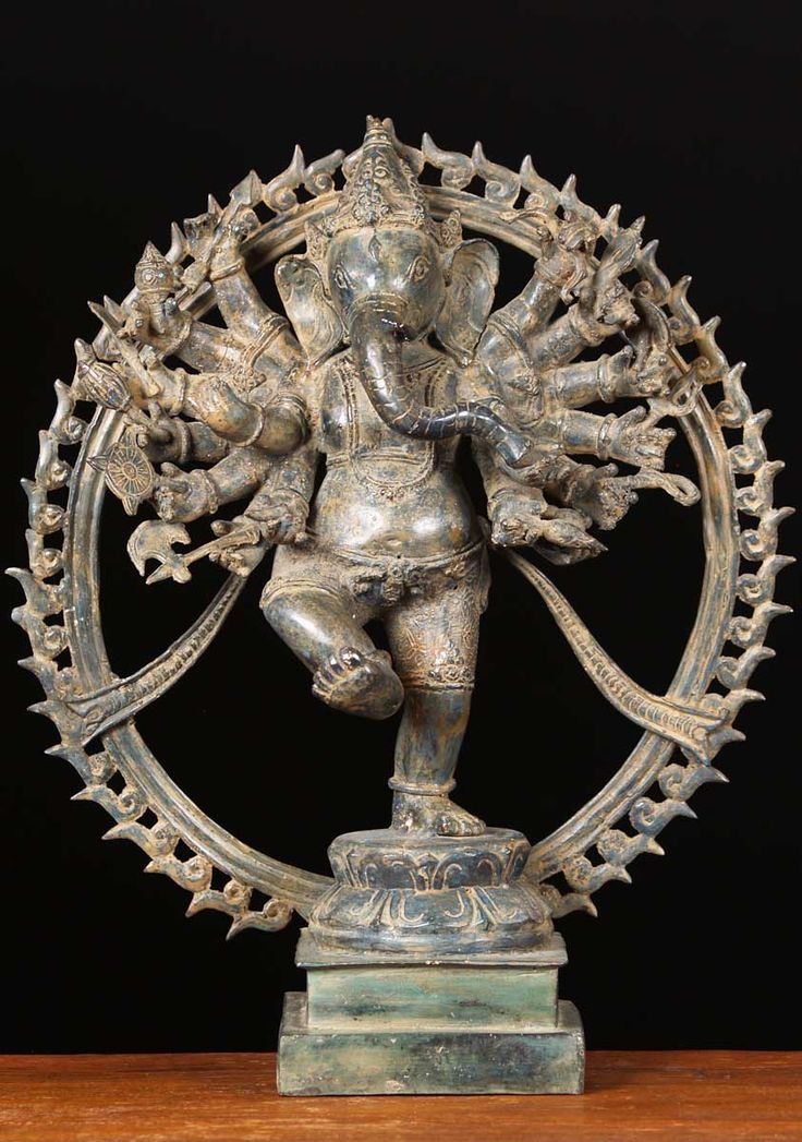 Balinese style dancing Ganesh statue.  Ganesh has 16 arms that are displayed in a fan like shape each holding a weapon or symbol of Ganesh. Ganesh is depicted inside a fiery ring much like the the prahabhamandala surrounding his father, Shiva in the form of Nataraja.  His right leg is lifted high. Ganesh usually is portrayed as being light on his feet in dance.  However, this sculpture portrays more of his elephant nature as being heavy on his feet.  A unique sculpture!