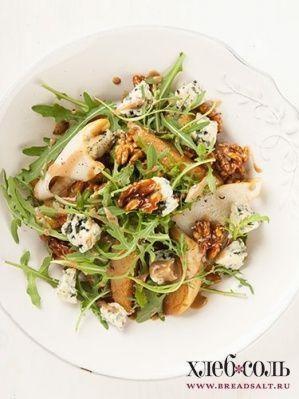 Рукколу заправьте оливковым маслом, солью, перцем, смешайте с крупными кусочками сыра и тонкими ломтиками груши. Перемешайте, разложите по тарелкам вместе с карамелизованной грушей и орехами и подавайте.