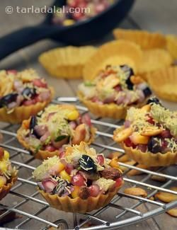 Every bite of this Fruit Tart Chaat makes you stop for a moment and marvel at its multiple dimensions! It is dainty and handy, served as a tart. It has the flavour and crunch of a chaat, and it has the exciting zing of tangy fruits too! This unique preparation features a tongue-tickling fruit chaat packed into tiny tarts and garnished with sev and peanuts.