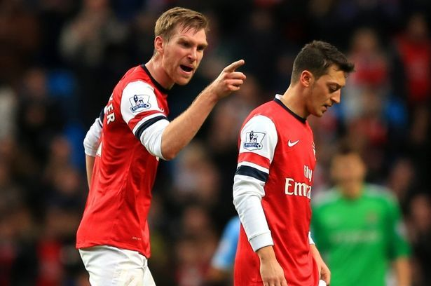 Per Mertesacker shouts at Ozil after his compatriot failed to applaud the travelling Arsenal fans.