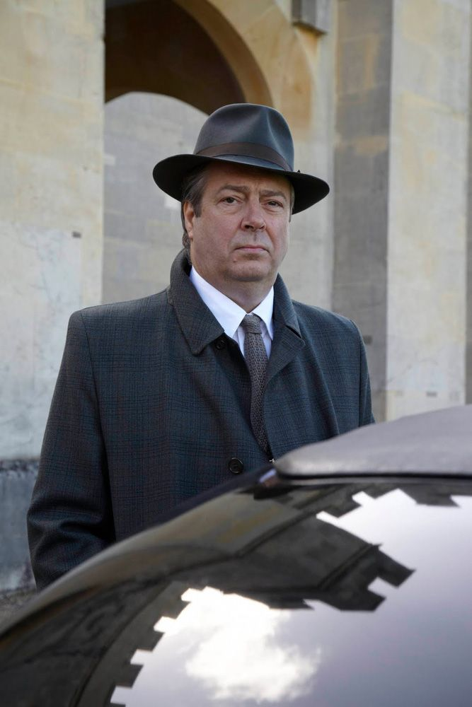 Roger Allam as Fred Thursday. Leaning on a car. Part of a series.