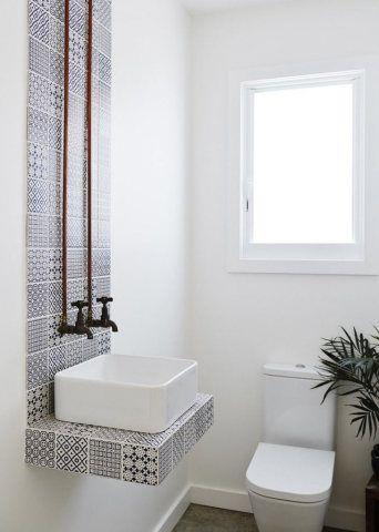 O mural de azulejos é o ponto central deste lavabo, combinado com uma cuba simples em branco e com canos expostos em cobre provenientes do teto.