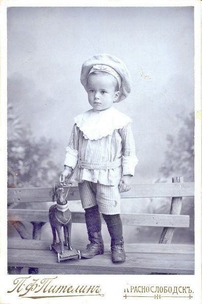 Small boy with a barret and a toy horse.