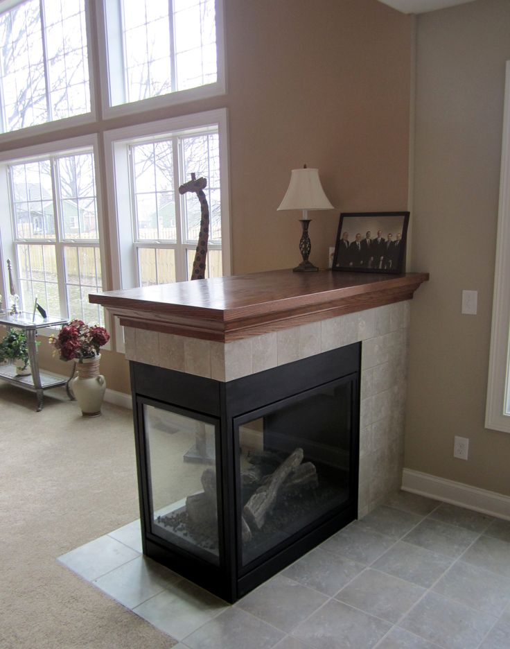 Three-sided fireplace with tile surround and oak mantle top! More
