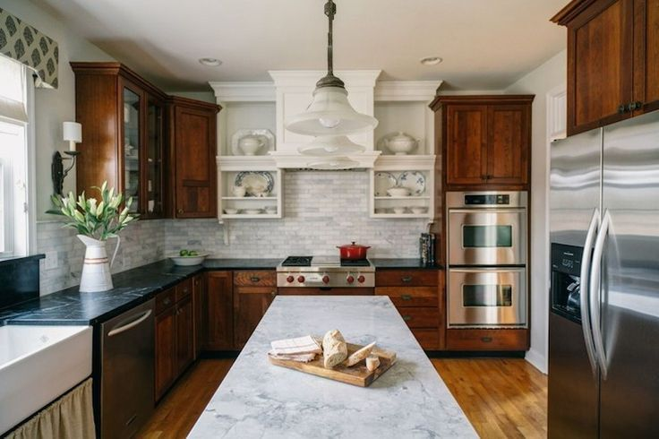 cherry, soapstone, white     Beautiful kitchen with cherry cabinets topped with soapstone countertops and white marble linear tiled backsplash framing skirted farmhouse sink below window dressed in valance.