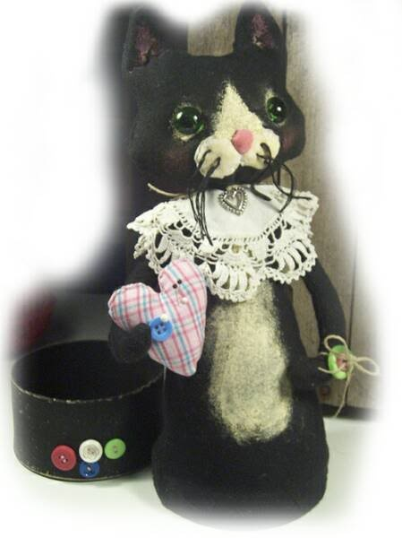 Painted muslin folk-art kitty with vintage lace collar, holding heart pin cushion and standing on button box lid.