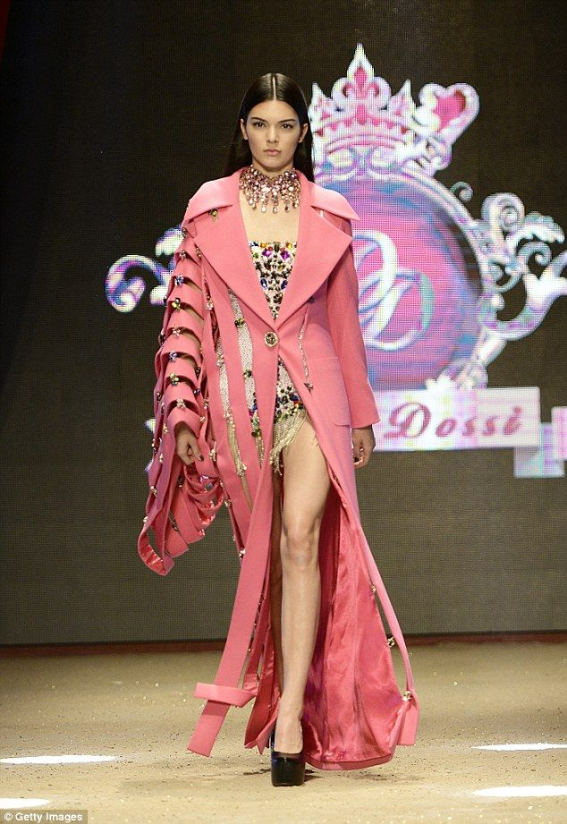 Interesting: Another of the 19-year-old's catwalk looks included a long salmon pink coat with oversized cut-out sleeves and a tiny bejewelled bodice