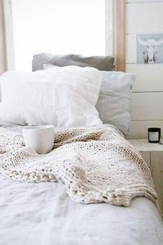 Cozy bedroom style idea: mixed pastel and white bed linens, a chunky handknit oversize throw blanket in natural wool and an oversize coffee mug -- breakfast in bed inspiration!