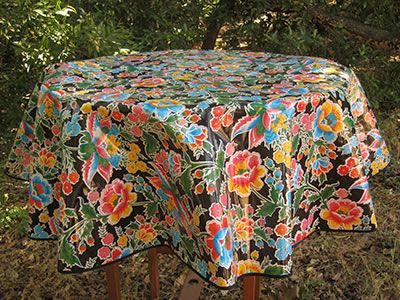 Round Primavera On Black Mexican Oilcloth Tablecloth In A Park Like Setting