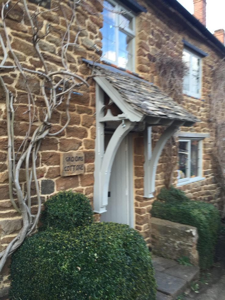Canopy porch in Oxfordshire with stone slates, elliptical brackets and trefoil gable.