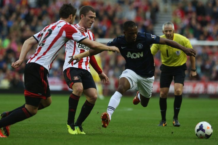Patrice Evra of Manchester United in action with Craig Gardner