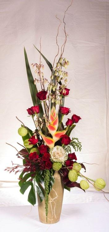Arreglo de heliconia con lechuga blanca, bombis y rosas rojas con follajes rojos diferentes.