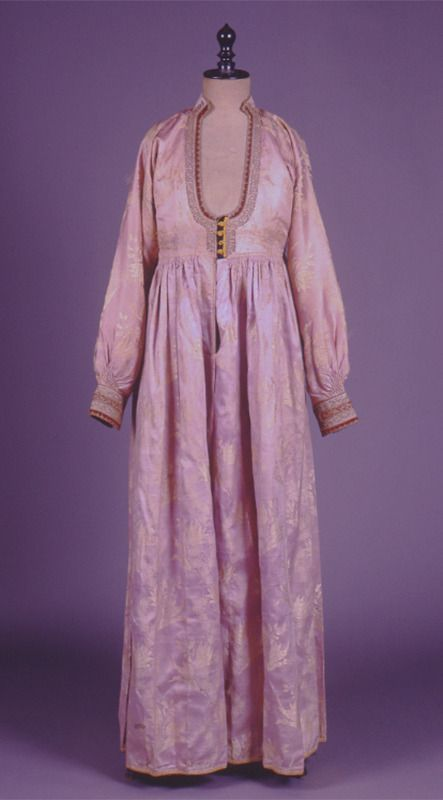 """""""Foustani"""". Dress. H. 1.40 m. Naoussa, Macedonia, Greece. Early 20th century. Peloponnesian Folklore Foundation Collection, Nafplion. Donated by Ioanna Papantoniou. 1976.6.242. """"Foustani"""". Long-sleeved lilac brocade dress with woven in white floral..."""