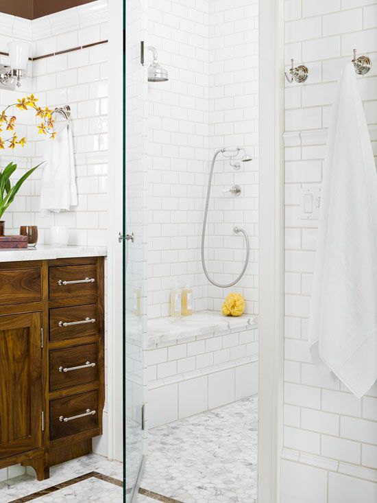 White Tile Bathway to keep brown vanity.Here, walls wrapped in white subway tiles mingle with marble tile floors. Rich brown wall color and a handsome walnut vanity balance the white backdrop and make the room feel cozy. A band of dark marble on the floor mimics the delicate line of brown tile on upper walls.