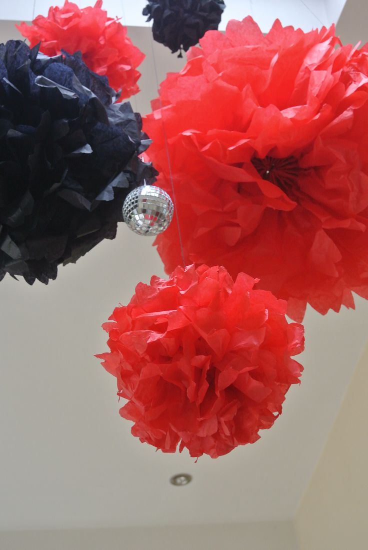 Red and black tissue paper pompoms, suspended from the ceiling with a disco ball or two!