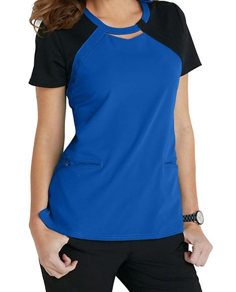Let your Careisma shine with the keyhole color block scrub top from the new Careisma by Sofia Vergara collection.  This modern fit top is designed with contrast knit contour panels that will  flatter your shape.  Two angled pockets come in handy to hold your accessories.  The soft, stretch fabric moves with you and feels great to wear.  Features a removable wristlet in the inside right pocket.   Careisma By Sofia Vergara Fearless Keyhole Color Block Scrub Tops  V-neck  Two angled pockets…