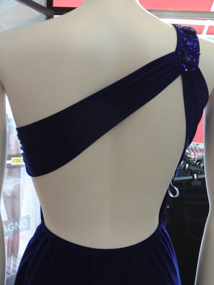 V-1011 - vestito monospalla in morbida viscosa, drappeggiato sul seno preformato (estraibile), profondo scollo sulla schiena, fondo assimmetrico con punta e spacco profondo a sinistra. Spallina impreziosita da je e strass. Taglia unica, vestibilità S/M.