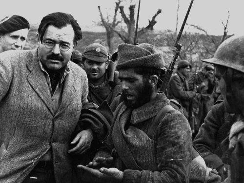 Ernest Hemingway, photographed by his good friend (and fellow correspondent) Robert Capa, somwhere on the Aragon front with Republican soldiers... Spanish Civil War, 1936-1939