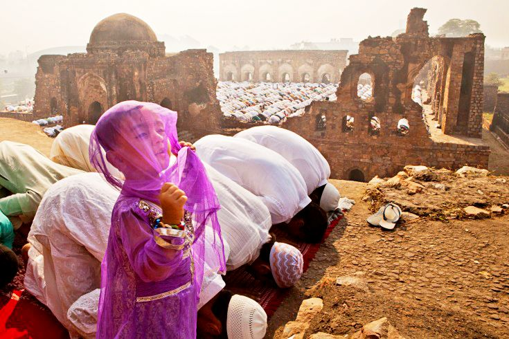 A young Indian muslim girl gestures during Friday prayers in New Delhi, India.