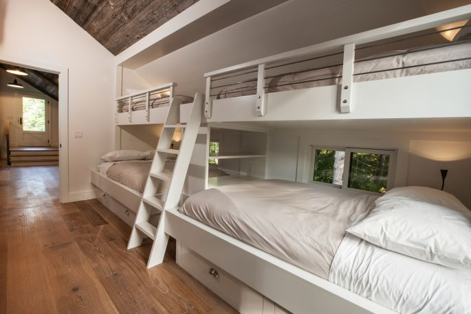 """Built-in bunk beds are a big trend in country houses and weekend retreats, says James Dixon of JDArchitect, who has offices in New York and Portland, Oregon. """"It's a way to pack in lots of extra accommodation into one room. Families with kids especially love the set-up. But when you throw all the adults together it can become quite the party."""" The mattresses on the upper beds sit on a secondary raised platform so that the base is not visible to those underneath. Photograph: John…"""