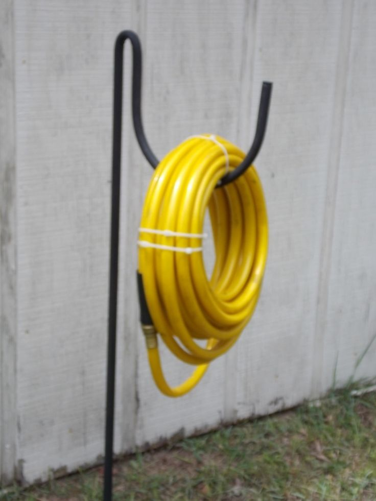 I FINALLY FOUND IT! ... AND AT AN EXCELLENT PRICE. the lazy scroll - Garden hose holder black wrought iron, $15.95 (http://www.thelazyscroll.com/garden-hose-holder-black-wrought-iron/)