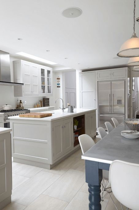 White Clean Kitchen Design - A white island contrasts nicely with colored table legs