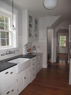 Clean lines in a 1930s Colonial Revival.  Brackets under cabinets, tile up wall, farmhouse sink